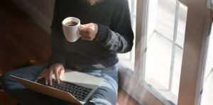 A remote worker sitting cross legged on the floor at home with a laptop on their lap and a cup of coffee in their hand